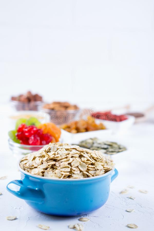 Oat flakes in blue bowl and various delicious ingredients for healthy breakfast on the kitchen table. stock photography