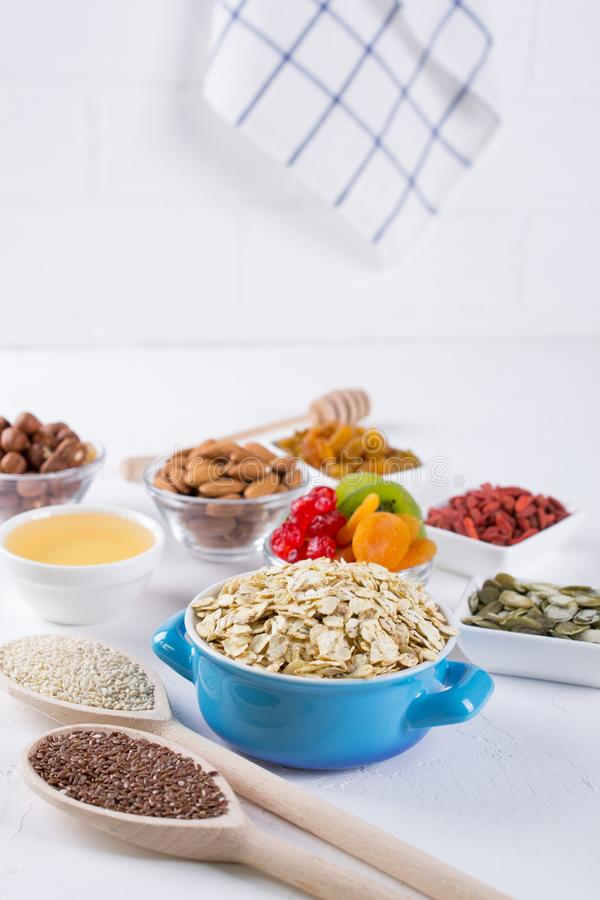 Oat flakes in blue bowl and various delicious ingredients for healthy breakfast on the kitchen table. royalty free stock image