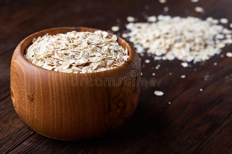 Oat flakes in bowl and wooden spoon isolated on wooden background, close-up, top view, selective focus. stock photo