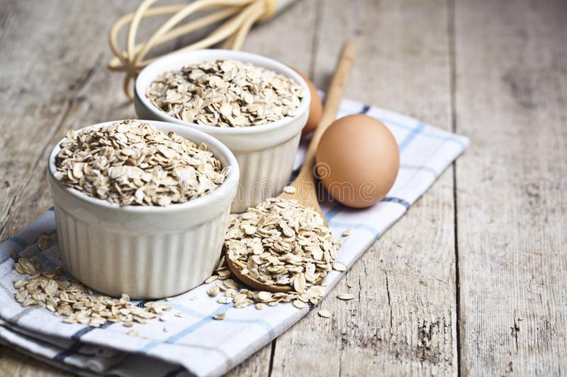 Oat flakes in ceramic bowls and wooden spoon and fresh chicken eggs on rustic wooden table background stock photography