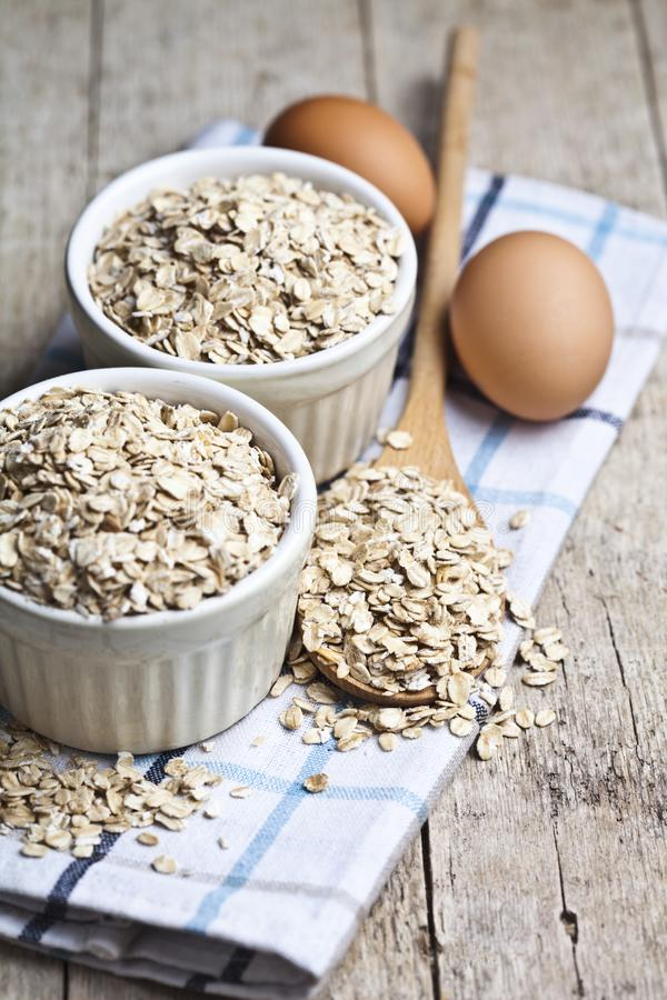 Oat flakes in ceramic bowls and wooden spoon and fresh chicken eggs on rustic wooden table background stock photo