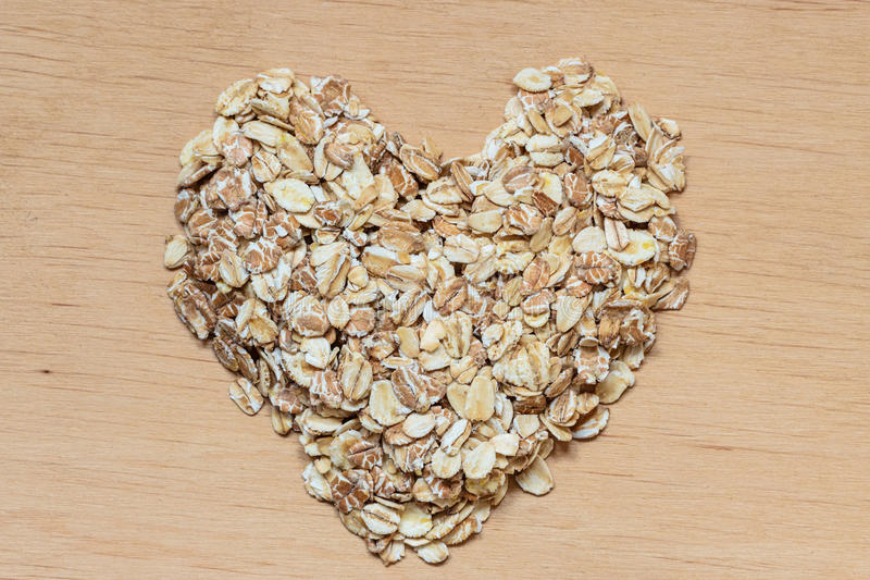 Oat flakes cereal heart shaped on wooden surface. Dieting healthcare concept. Oat cereal heart shaped on wooden surface. Healthy food for lowering cholesterol royalty free stock images