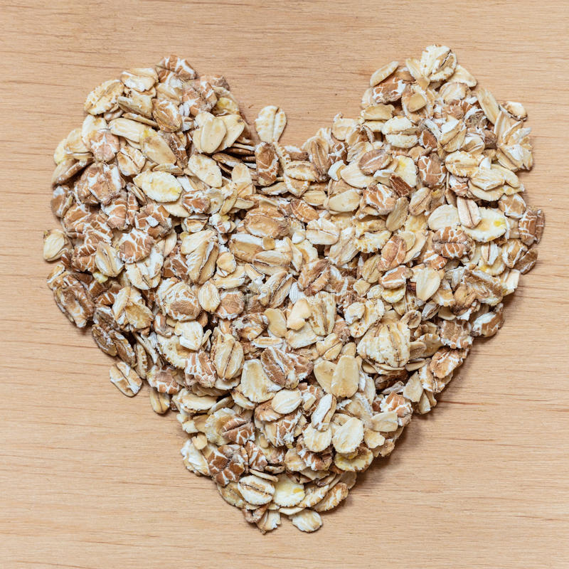 Oat flakes cereal heart shaped on wooden surface. Dieting healthcare concept. Oat cereal heart shaped on wooden surface. Healthy food for lowering cholesterol royalty free stock photos