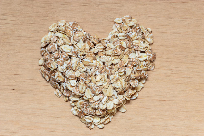 Oat flakes cereal heart shaped on wooden surface. Dieting healthcare concept. Oat cereal heart shaped on wooden surface. Healthy food for lowering cholesterol stock photo
