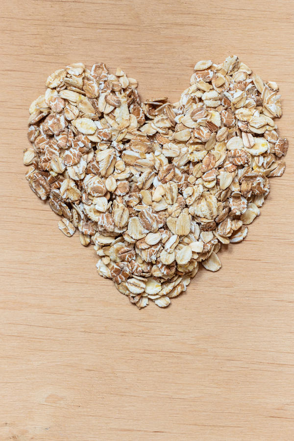Oat flakes cereal heart shaped on wooden surface. Dieting healthcare concept. Oat cereal heart shaped on wooden surface. Healthy food for lowering cholesterol royalty free stock photography