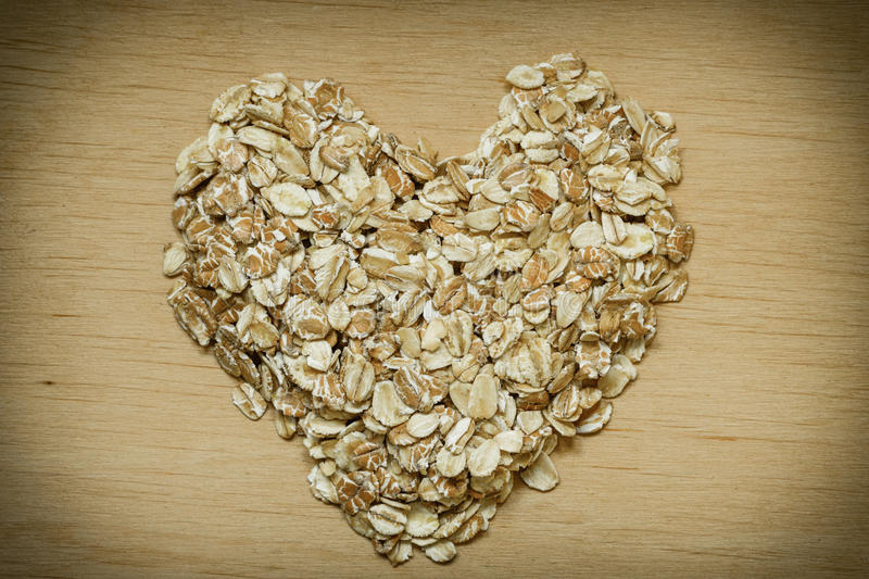 Oat flakes cereal heart shaped on wooden surface. Dieting healthcare concept. Oat cereal heart shaped on wooden surface. Healthy food for lowering cholesterol stock photography