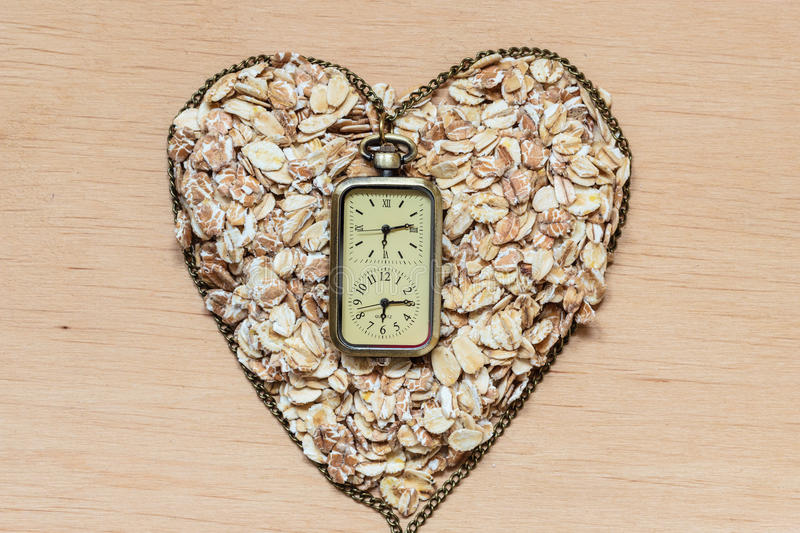 Oat flakes cereal heart shaped on wooden surface. Time for dieting healthcare concept. Oat cereal heart shaped and watch on wooden surface. Healthy food for royalty free stock photos