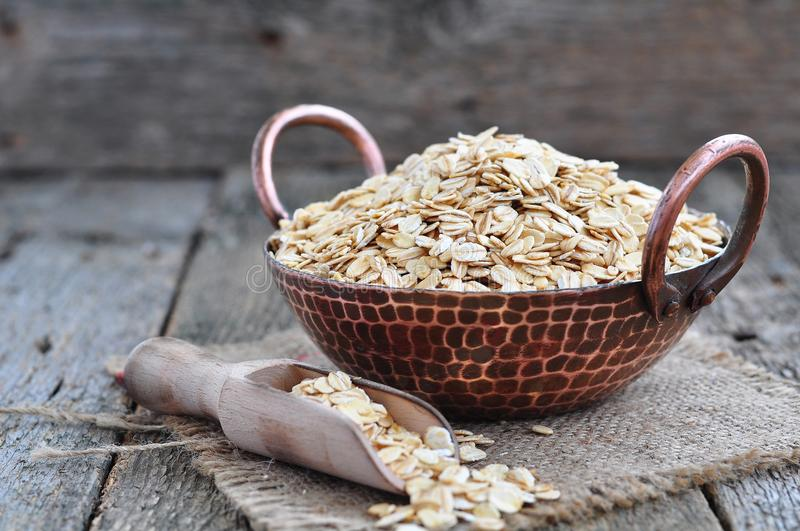 Oat flakes in a copper plate on a wooden table. Dinner royalty free stock image