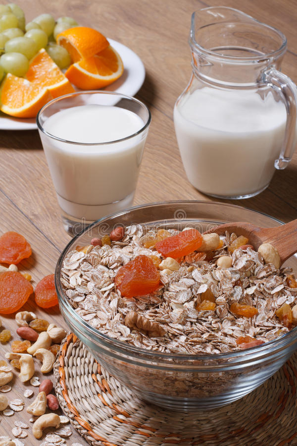 Oat flakes with dried fruit and milk and fresh fruit. Vertical royalty free stock photography