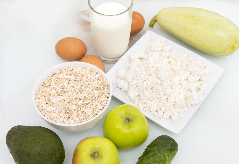 Oat flakes, a glass of milk, cottage cheese, eggs, apples, avocado, zucchini, cucumber, vegetables and fruits, healthy food. Oat flakes, glass of milk, eggs stock photo