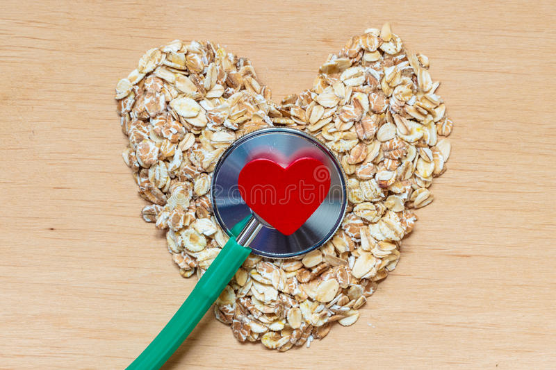 Oat flakes heart shaped and stethoscope. Dieting healthcare concept. Oat cereal heart shaped, stethoscope on wooden surface. Healthy food for lowering stock photos