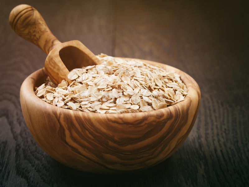 Oat flakes in wood bowl on oak table. Vintage toned royalty free stock image