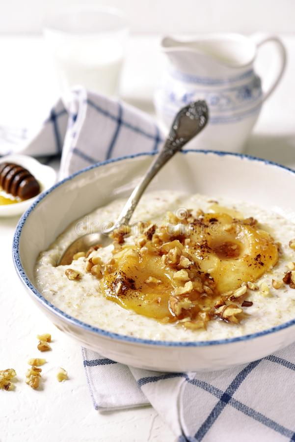 Oat porridge with caramelized pear and nuts. Oat porridge with caramelized pear and nuts in a vintage bowl on a light slate,stone or concrete background royalty free stock image
