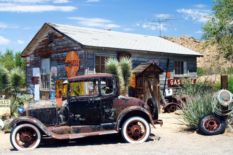 OATMAN亚利桑那,美国- 8月7日 2009年:在被放弃的木历史的老加油站前面的美国葡萄酒汽车 免版税库存图片