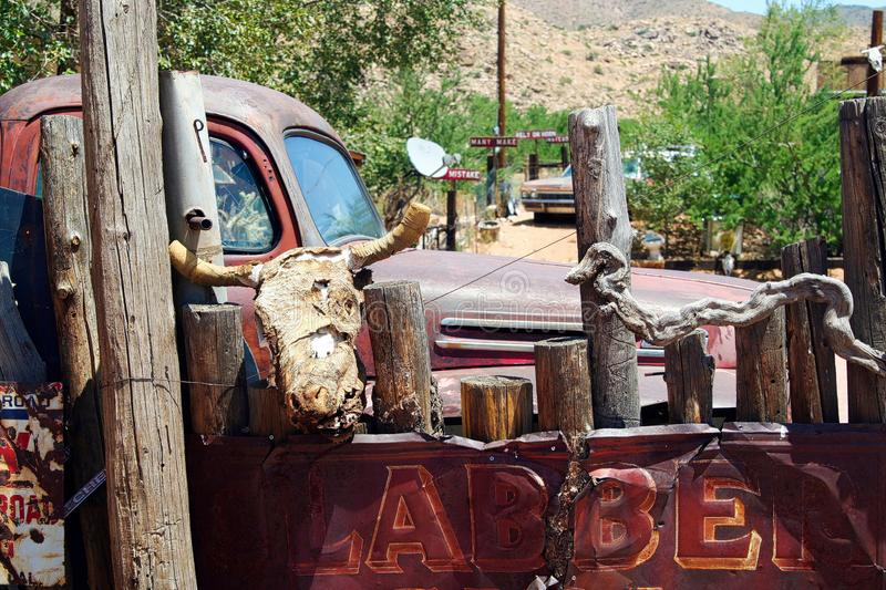 OATMAN ARIZONA, USA - AUGUST 7. 2009:  View on red rusty moonshine vintage car with skull of buffalo hanging on a fence in stock photo
