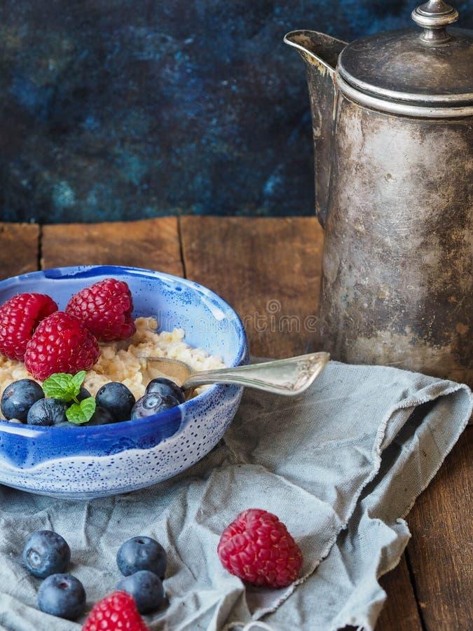 Oatmeal κουάκερ με τα βακκίνια και τα σμέουρα στοκ φωτογραφία με δικαίωμα ελεύθερης χρήσης
