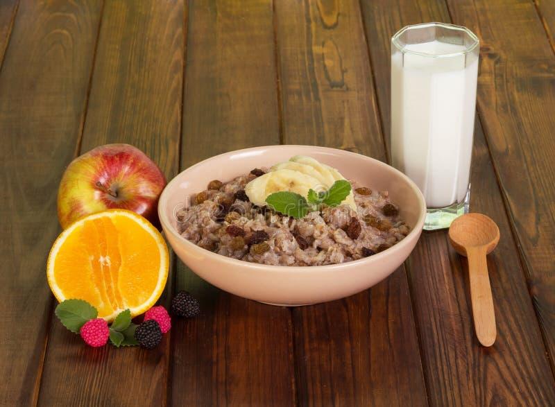 Oatmeal κύπελλων με τις σταφίδες, τα φρούτα, το γάλα γυαλιού και το κουτάλι στοκ εικόνες