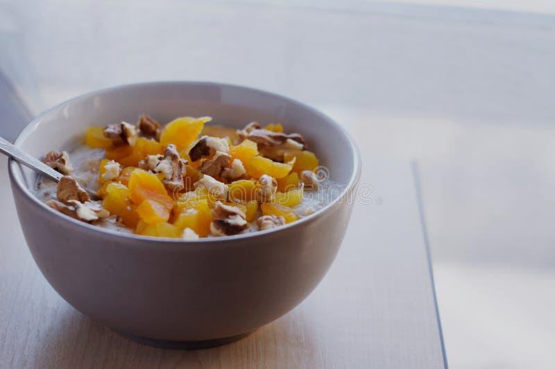 Oatmeal με τα ξηρά βερίκοκα και τα ξύλα καρυδιάς στοκ εικόνα