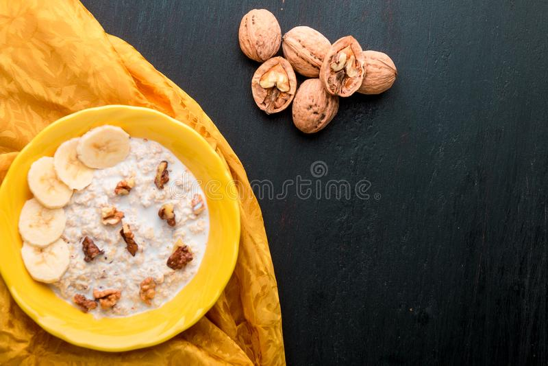 Oatmeal με τα ξύλα καρυδιάς και την μπανάνα στοκ εικόνα
