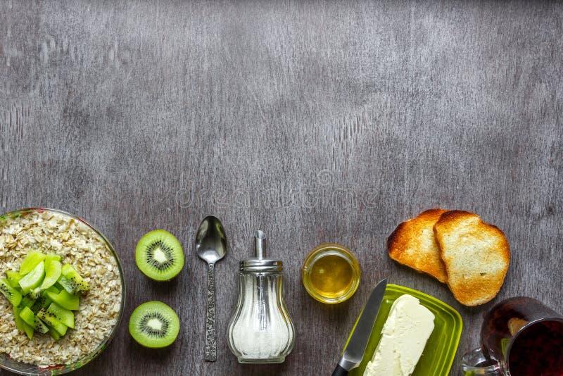 Oatmeal με το ακτινίδιο, φρυγανιά με το βούτυρο και μέλι σε έναν ξύλινο πίνακα Η έννοια ενός υγιούς προγεύματος στοκ εικόνες