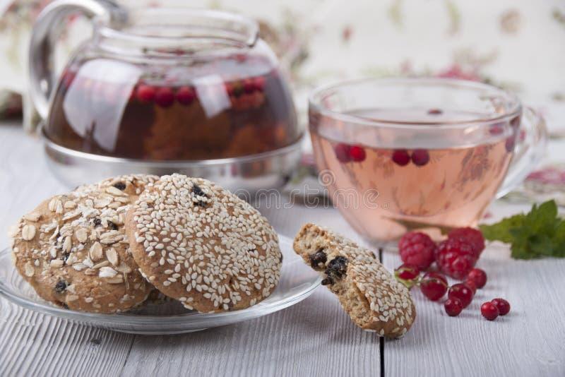Oatmeal μπισκότα με το σουσάμι και το τσάι σε ένα φλυτζάνι και teapot στοκ φωτογραφία