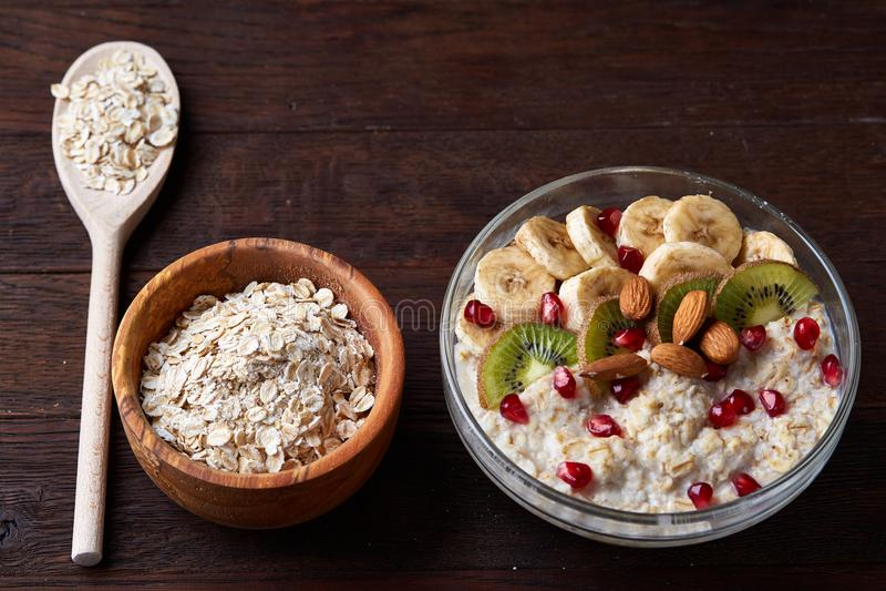 Oatmeal προγευμάτων διατροφής με τα φρούτα, το κύπελλο και το κουτάλι με τη βρώμη ξεφλουδίζει, εκλεκτική εστίαση, κινηματογράφηση στοκ φωτογραφία