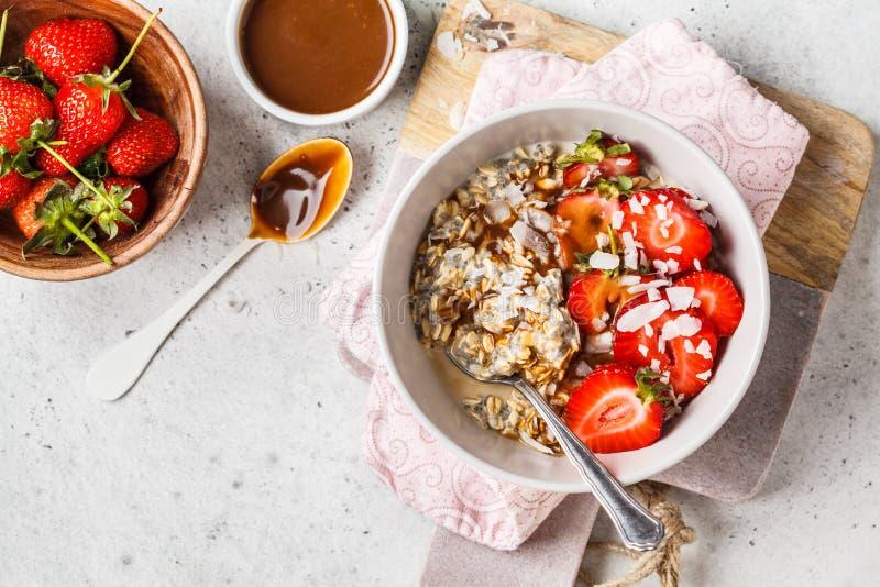 Oatmeal προγευμάτων Vegan με τους σπόρους, τα μούρα, τους σπόρους και την καραμέλα chia στο άσπρο κύπελλο, διάστημα αντιγράφων στοκ εικόνα με δικαίωμα ελεύθερης χρήσης