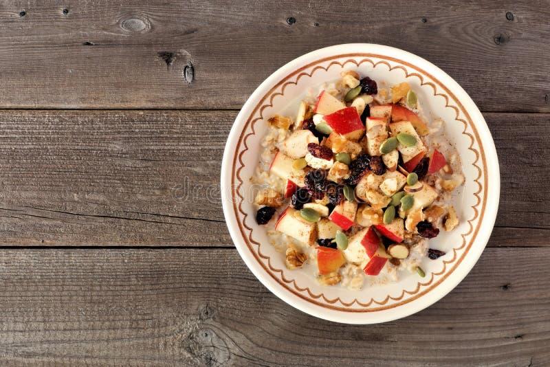 Oatmeal φθινοπώρου με τα μήλα, τα τα βακκίνια, το σπόρο και τα καρύδια στοκ εικόνες με δικαίωμα ελεύθερης χρήσης