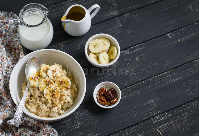 Oatmeal with banana, caramel sauce and pecan nuts in a white bowl on a dark wooden surface stock photography