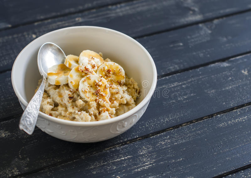 Oatmeal with banana, caramel sauce and pecan nuts in a white bowl on a dark wooden surface stock image