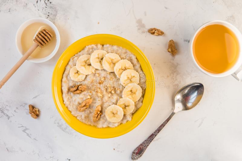 Oatmeal with banana and honey. Porridge in a yellow bowl top vie royalty free stock images