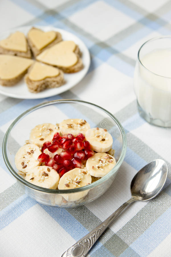 Oatmeal with banana and pomegranate, cheese sandwiches and a glass of milk for breakfast royalty free stock photography