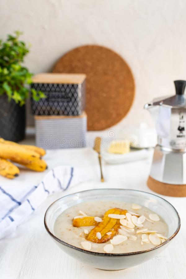 Oatmeal with bananas and almonds, moka coffee maker. Table with served breakfast, oatmeal with bananas and almonds, moka coffee maker stock photos