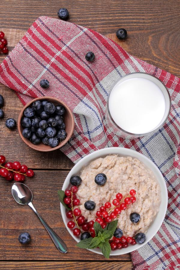 Oatmeal with berries and milk in a bowl on a brown wooden table. breakfast. healthy food. stock photography