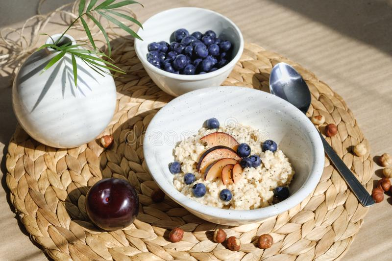 Oatmeal with berries, nuts, plums and chia seeds. royalty free stock photography