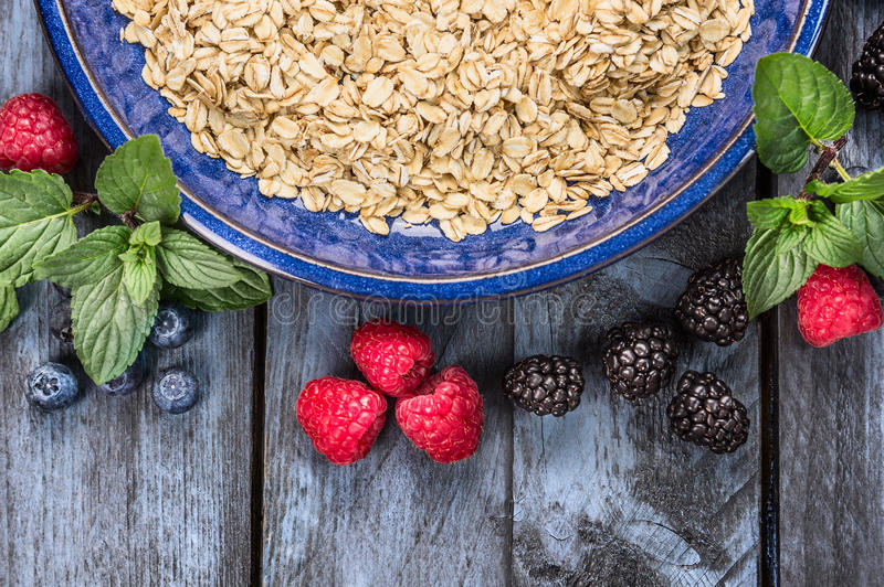 Oatmeal in blue bowl with berries on rustic wooden background, top view,healthy food stock image