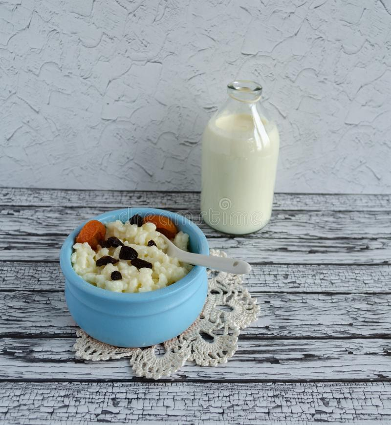Oatmeal in a blue plate, milk, dried fruits stock image