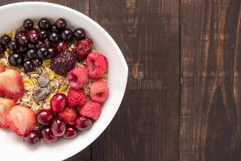 Oatmeal in bowl topped with fresh blueberries, cranberries, strawberries, raspberries, blackberries for healthy breakfast. Oatmeal in bowl topped with fresh royalty free stock image