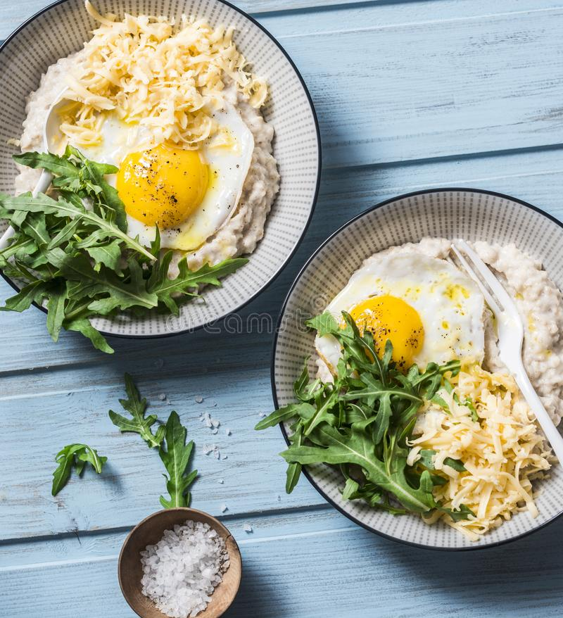 Oatmeal with cheese, fried egg and arugula. Delicious, nutritious breakfast on a blue background stock image