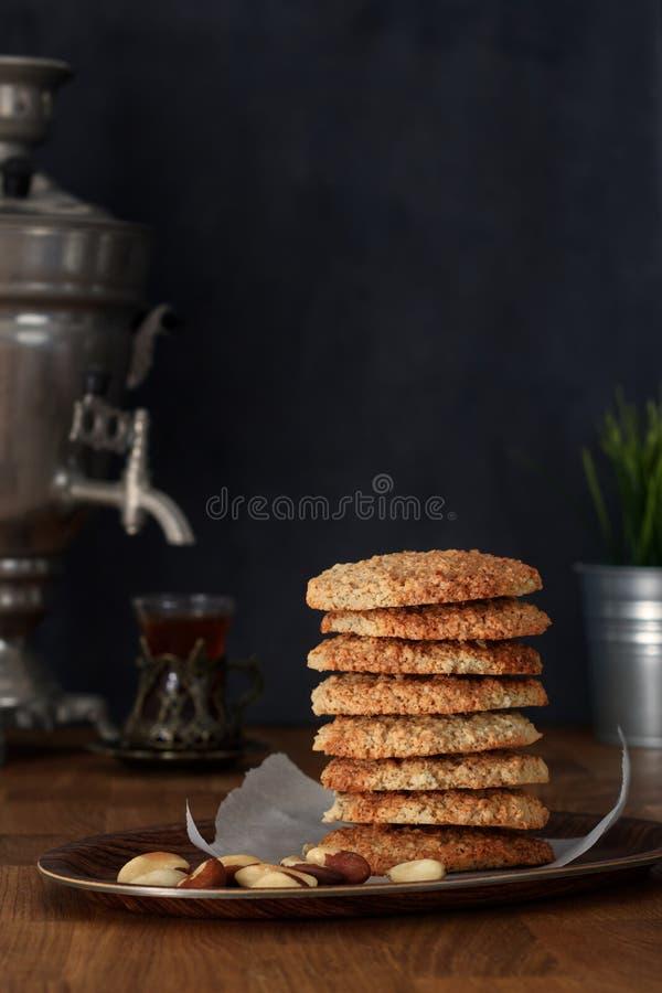 Oatmeal ciastka z Brazylijskimi dokrętkami i herbatą przy samowarem na drewnianym stole fotografia stock