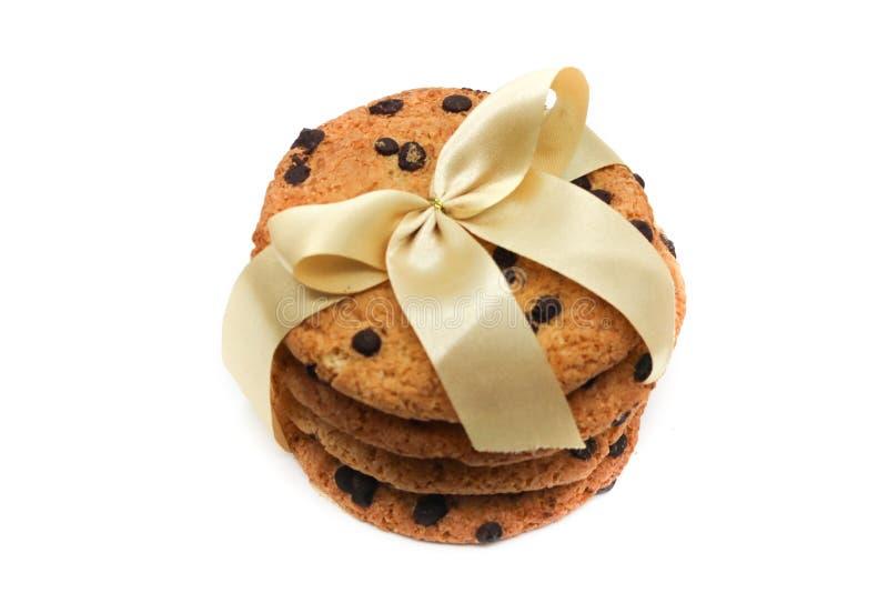 Oatmeal ciastka z czekoladowymi kroplami, wi?zanymi z z?otym faborkiem, odizolowywaj?cym na bia?ym tle fotografia stock