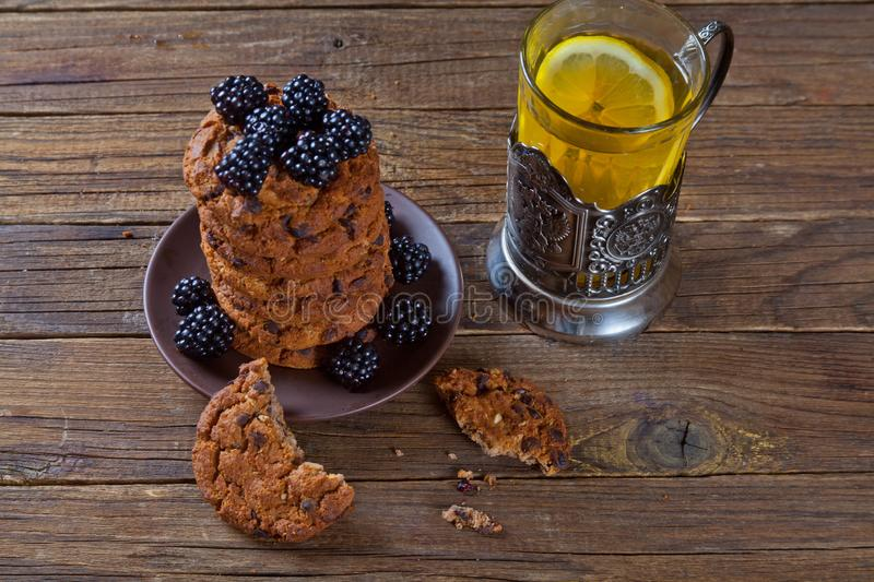 Oatmeal cookies with blackberries and a glass of tea stock photo