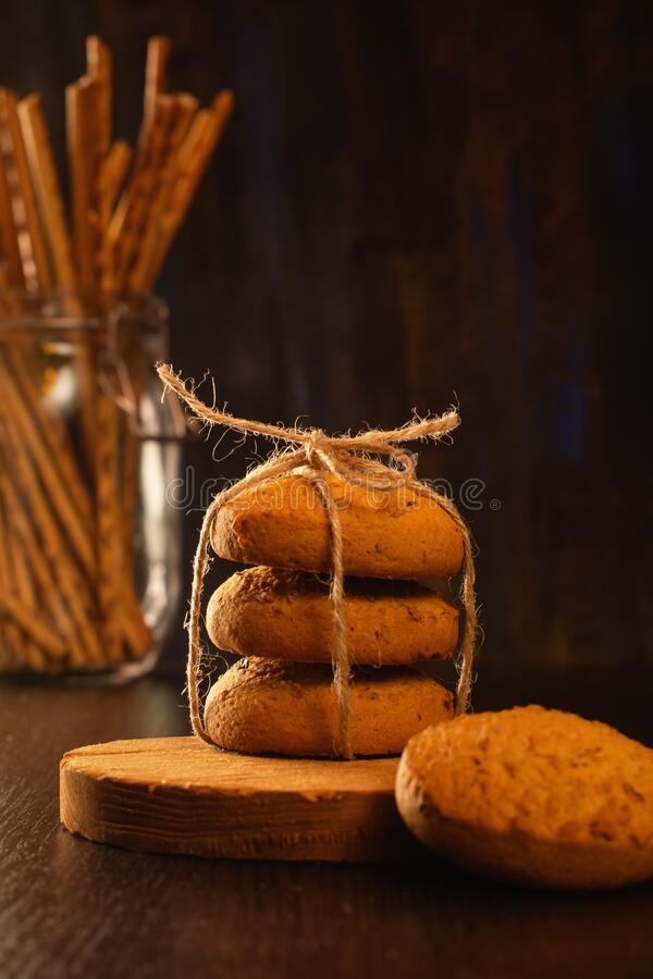 Oatmeal cookies and chopsticks. Still life in vintage style. Brown background stock photography