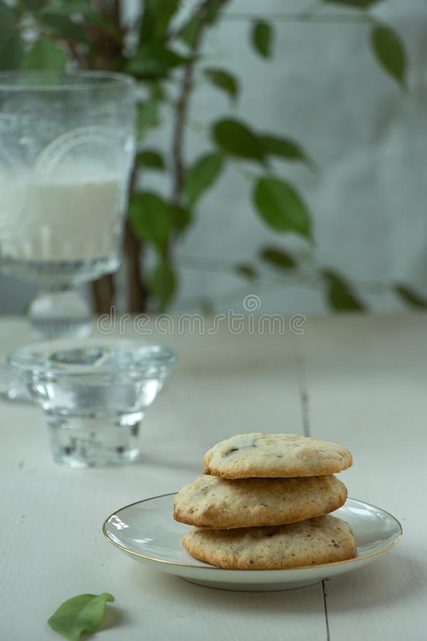 Three Oatmeal cookies at porcelain plate and wooden background, light and white photography in a rustic style. Oatmeal cookies with a glass of milk, light and stock photo