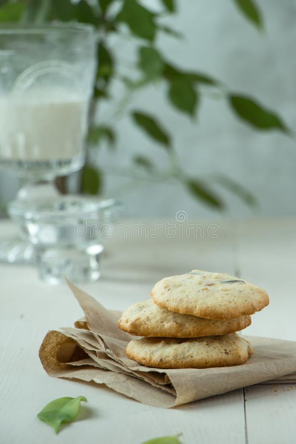 Three Oatmeal cookies at paper and wooden background, light and white photography in a rustic style. Oatmeal cookies with a glass of milk, light and white royalty free stock photos