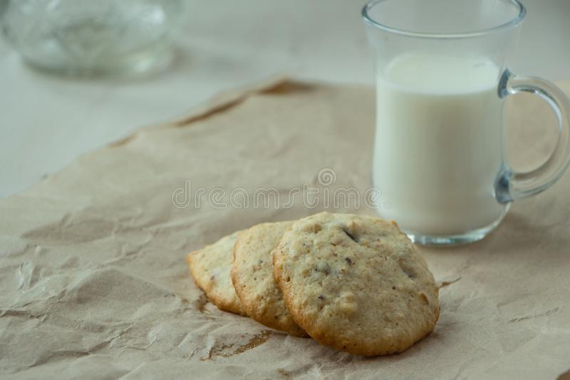 Three Oatmeal cookies with small glass of milk at paper, light and white photography in a rustic style. Oatmeal cookies with a glass of milk, light and white stock photography