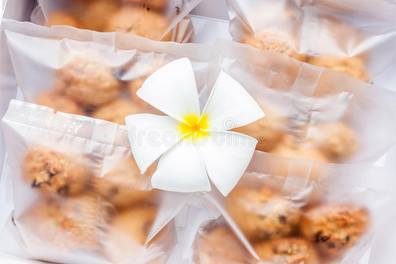Oatmeal cookies in plastic bag package with flower decoration. royalty free stock image