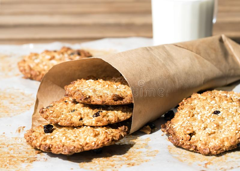 Oatmeal Cookies with Raisins and Glass of Milk for Breakfast. Some Cookies on Parchment Paper. Gorizontal orientation royalty free stock image