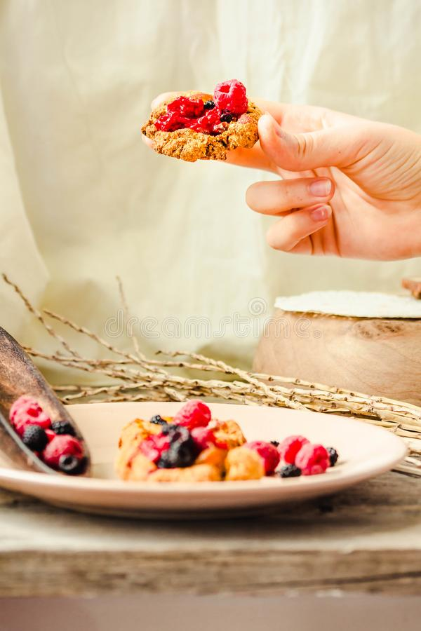 Oatmeal cookies with raspberry jam and date caramel in the hands of a young woman. The process of eating stock image
