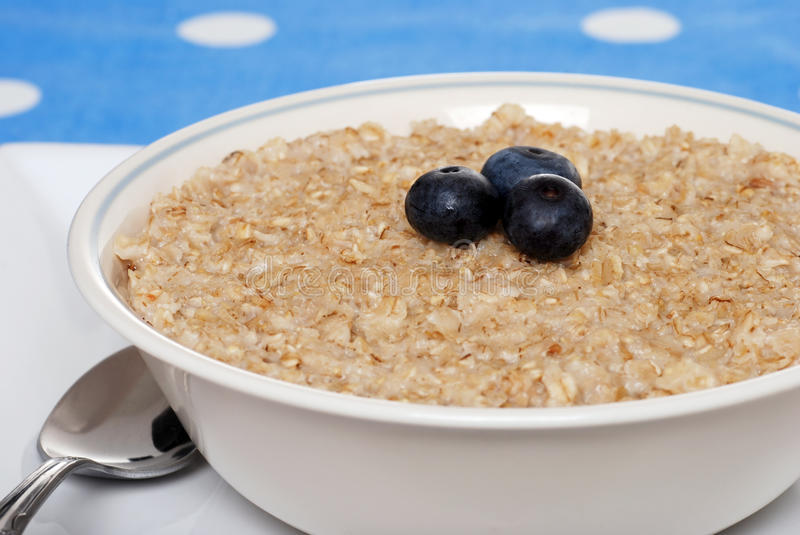 Oatmeal do close up com foco das uvas-do-monte em bagas fotografia de stock royalty free